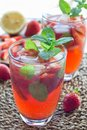 Glass of refreshing iced tea with strawberries and mint, vertica Royalty Free Stock Photo