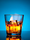 Glass of scotch whiskey and ice on a blue