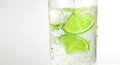 Glass of soda with lime on white background low aperture Royalty Free Stock Image