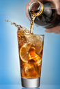 Glass of splashing iced tea with lemon on blue background Royalty Free Stock Photo