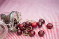 Glass storage jar full of fresh cherries tasty in Stock Photo