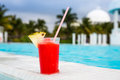 Glass of strawberry daiquiri cocktail standing on the swimming pool ledge in an tropical resort Stock Photos