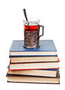 Glass of tea on stack of books isolated white background Royalty Free Stock Photo