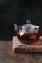 Glass teapot with black tea hot standing on clay board over old wooden background copy space Stock Photo
