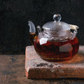 Glass teapot with black tea hot standing on clay board over old wooden background copy space square image Royalty Free Stock Photos