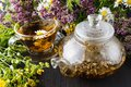 Glass teapot and cup with green tea on old wooden table with fresh herbs Royalty Free Stock Photo