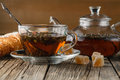 Glass teapot and cup with herbal tea on old wooden table Royalty Free Stock Photo
