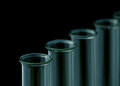 Glass test tubes against black background selective focus Stock Photo
