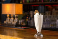 Glass of vanilla milkshake on bar counter Stock Photos