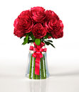 Glass vase full of big red roses with ribbon on white reflective surface and white background clipping path included Royalty Free Stock Photos