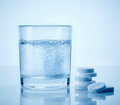 Glass of water and aspirin pills Royalty Free Stock Image