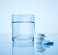 Glass of water and aspirin pills Stock Photography
