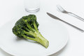 Glass of water, fork, knife and broccoli on the plate Royalty Free Stock Photo