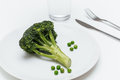 Glass of water, fork, knife, plate with peas and broccoli Royalty Free Stock Photo