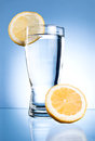 Glass of water and lemon on a blue Royalty Free Stock Photo