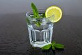 A glass of water with lemon and mint between drops of water. Summer refreshing drink. Royalty Free Stock Photo