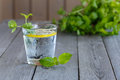 Glass of water and mint on a wooden table