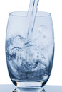 Glass with water is poured into a symbol photo for drinking freshness demand and consumption Stock Photos