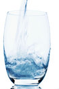 Glass with water is poured into a symbol photo for drinking freshness demand and consumption Stock Images