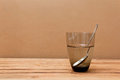 Glass of water and spoon on wooden table refraction effect Stock Photo