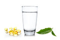 Glass of water wiith green tea leaf and fish oil  on whi Royalty Free Stock Photo
