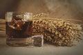 Glass whiskey on background with wheat straws toning photo Royalty Free Stock Photo