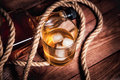 Glass of whiskey with ice, a bottle of single malt whiskeys Royalty Free Stock Photo