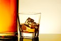 Glass of whiskey with ice cubes near bottle on table with reflection warm tint atmosphere time relax whisky Stock Photo