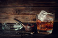 Glass of whiskey with ice and pipe on a wooden background. Royalty Free Stock Photo