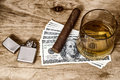 Glass of whiskey and money a with cuban cigar lighter on a wooden table Stock Images