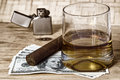 Glass of whiskey and money a with cuban cigar lighter on a wooden table Royalty Free Stock Images