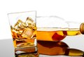 Glass of whiskey near bottle on black table with reflection time relax whisky Royalty Free Stock Images