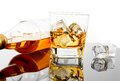Glass of whiskey near bottle and ice cubes on black table with reflection time relax whisky Stock Photography
