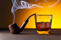 Glass of whiskey and pipe on a wooden table Royalty Free Stock Photo