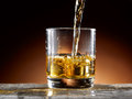 Glass of whiskey poured into the Royalty Free Stock Photos