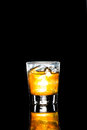 A glass of whiskey on the rock in portrait orientation against a dark background rocks Royalty Free Stock Image