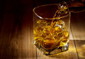 Glass of whiskey on wooden table Stock Photography