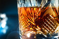 Glass of whisky close view on dark purple background Royalty Free Stock Photo