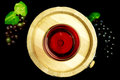 Glass of white wine on a barrel red black background with bunches grapes Royalty Free Stock Photography