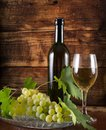 Glass with white wine, black bottle and grapes in bowl decorated with vine Royalty Free Stock Photo
