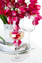 Glass of white wine and a festive table setting with bouquet bright pink tulips in vase isolated Stock Photos