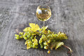 Glass of white wine and grapes a bunch Royalty Free Stock Image