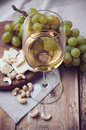 Glass of white wine grapes cashew nuts and soft cheese a on a wooden board rustic style Royalty Free Stock Image