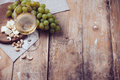 Glass of white wine grapes cashew nuts and soft cheese a on a wooden board rustic style background Royalty Free Stock Images