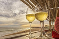 Glass of white wine overlooking the beach with sunset Royalty Free Stock Photo