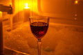 A glass of wine and bubble bath red by candle light Royalty Free Stock Photos