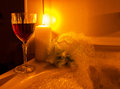 A glass of wine and bubble bath red by candle light Stock Images