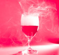 Glass of wine with smoke on red back ground Royalty Free Stock Image
