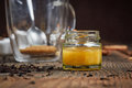 Glass of yellow honey in front of a teaglass Royalty Free Stock Photo