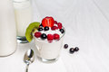 Glass of yogurt with raspberry black currants strawberrie and kiwi on wooden background Stock Photography